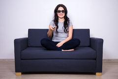 3d television concept - young woman sitting on sofa and watching Stock Images