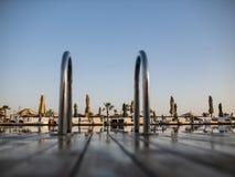 D?tendez pr?s de la piscine avec la balustrade, les lits pliants, les canap?s du soleil et les parasols attendant des touristes d images libres de droits