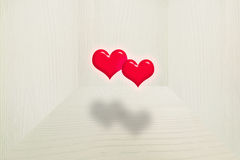3d, two red hearts floating in the air with soft shadow in the vintage wooden room Royalty Free Stock Photography