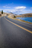 Długa Dwudrogowa droga z jeziorem na stronie Zdjęcia Royalty Free