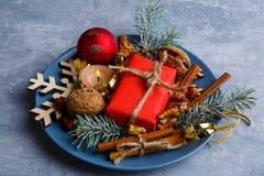 D'un plat bleu, des décorations de Noël faites de branches d'arbre de Noël, du boîte-cadeau, d'une petite bougie brûlante et de l photographie stock libre de droits