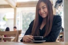 D'une belle café se tenant et potable femme asiatique avec se sentir décontracté en café Photo stock