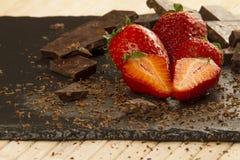 A d'une mani?re ordonn?e plac? des fraises sur un plat d'ardoise avec du chocolat coup? et a r?p? autour sur un fond en bois clai photo libre de droits