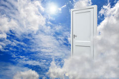 3D white door opened on nice sky background. With white clouds Stock Image