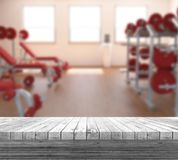 3D white wooden table looking out to a defocussed gym interior. 3D render of a white wooden table looking out to a defocussed gym interior Stock Photo