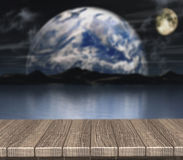 3D wooden table looking out to a defocussed night scene Stock Photos