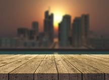 3D wooden table looking out to a fictional city landscape Royalty Free Stock Image