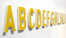 3d yellow alphabet lettering on a wall Stock Photo