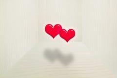 3d, zwei rote Herzen, die in die Luft mit weichem Schatten im hölzernen Raum der Weinlese schwimmen Lizenzfreie Stockfotografie