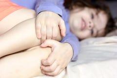 Daño y dolor de la sensación de la muchacha del niño, ella sostiene sus rodillas imágenes de archivo libres de regalías