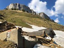 Daños a las granjas de la montaña causadas por las avalanchas nevosas en el verschneite Lawinen del durch de Schäden de la regió imagenes de archivo