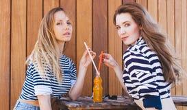 坐在夏天咖啡馆和饮料橙色饮料的两个时尚美丽的女孩通过从瓶的秸杆 晴朗的温暖的夏天da 库存图片