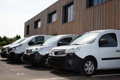 Da camionete branca do serviço de entrega da fileira os caminhões pequenos estacionam a parte dianteira da planta da distribuição imagem de stock
