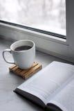 Da casa vida acolhedor ainda: copo do café ou do chá quente e livro aberto na soleira Conceito da educação, espaço da cópia gratu Fotos de Stock