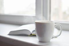 Da casa vida acolhedor ainda: copo do café ou do chá quente e livro aberto na soleira Conceito da educação, espaço da cópia gratu Imagens de Stock