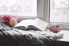 Da casa vida acolhedor ainda: copo do café quente, das flores da mola e do livro aberto com a manta morna na soleira primavera Imagem de Stock