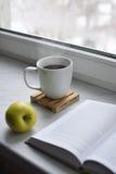 Da casa vida acolhedor ainda: copo do café quente e do livro aberto com a maçã verde na soleira contra a paisagem da neve fora Imagens de Stock Royalty Free