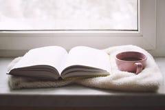 Da casa vida acolhedor ainda: copo do café quente e do livro aberto com a manta morna na soleira contra a neve Espaço da cópia gr Fotos de Stock