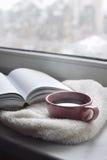Da casa vida acolhedor ainda: copo do café quente e do livro aberto com a manta morna na soleira contra a paisagem da neve fora Foto de Stock