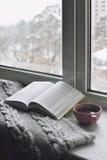 Da casa vida acolhedor ainda: copo do café quente e do livro aberto com a manta morna na soleira contra a paisagem da neve fora Imagens de Stock Royalty Free