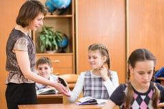 Da criança de confiscação da escola do professor o telemóvel na lição Imagem de Stock