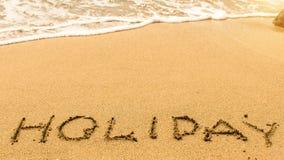 Día de fiesta - manuscrito en la arena en la línea de la resaca del mar Extracto Imagen de archivo libre de regalías