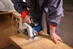 Da el carpintero que trabaja con la sierra circular Fotografía de archivo