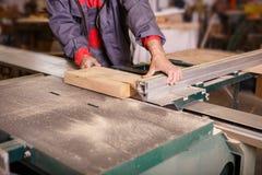 Da el carpintero que trabaja con una sierra circular Imagen de archivo libre de regalías