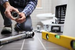 Da el fontanero en el trabajo en un cuarto de baño, sondeando servicio de reparación, como foto de archivo