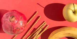 Da fruto el disco: Granada roja grande, manzana de oro, plátano fresco y palillos salados en rojo Foto de archivo libre de regalías