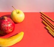Da fruto el disco: Granada roja grande, manzana de oro, plátano fresco y palillos salados en rojo Fotografía de archivo libre de regalías