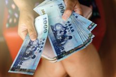 Da la mujer que cuenta los nuevos billetes de dólar de Taiwán Fotografía de archivo