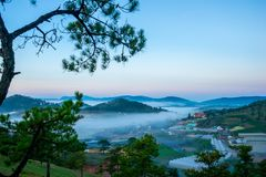 Da lat, lam dong, viet nam- feb 12, 2017: beautyful landscape of da lat city, a small vietnamese pagoda in fog and the pine hill Stock Images