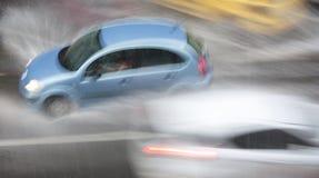 Día lluvioso en la ciudad: Los coches de conducción en la calle golpearon por el h Imágenes de archivo libres de regalías