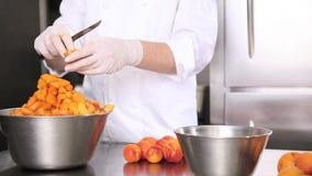 Da los albaricoques del corte del chef de repostería, prepara el atasco en cocina industrial almacen de video
