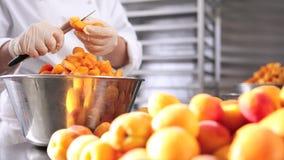Da los albaricoques del corte del chef de repostería, prepara el atasco en cocina industrial metrajes