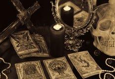 Da mágica a vida ainda com os cartões de tarô, o mirrow e o crânio no sepia tonificam Fotos de Stock