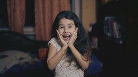 Da menina do gesto polegar sim acima da emoção da alegria e do sucesso da felicidade menina na sala de nivelamento que mostra os  vídeos de arquivo