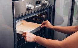 Da a mujer la panadería femenina que sostiene el pan fresco en el horno delantero Imagen de archivo libre de regalías