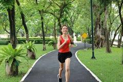Da mulher asiática do corredor da aptidão Relaxed música de escuta de sorriso e exercício de corrida no parque natural imagens de stock