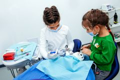 Da mulher vermelha adolescente pequena do disconto do ano novo do doutor da menina dos dentes do dentista das crianças do escritó imagens de stock royalty free