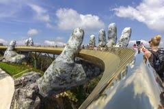 Da Nang, Вьетнам - 31-ое октября 2018: Туристы в золотом мосте, пешеходной тропе поднятой 2 гигантскими руками, раскрывают в июле стоковые изображения rf