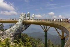 Da Nang, Вьетнам - 31-ое октября 2018: Туристы в золотом мосте, пешеходной тропе поднятой 2 гигантскими руками, раскрывают в июле стоковые изображения