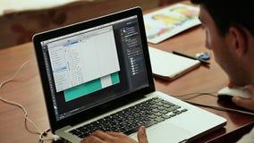 DA NANG VIETNAM - OKTOBER 8, 2016: En grabb arbetar på en design på en bärbar dator Arbete Apple Mac Book Pro lager videofilmer