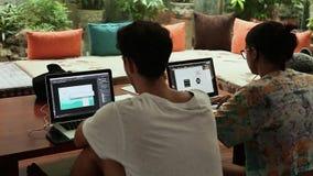 DA NANG VIETNAM - OKTOBER 8, 2016: En grabb och en flicka arbetar på en design på en bärbar dator Arbete Apple Mac Book Pro stock video