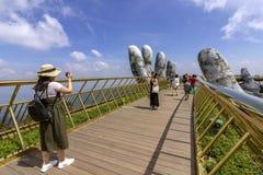 Da Nang, Vietname - 31 de outubro de 2018: Os turistas na ponte dourada, um passeio pedestre levantado por duas mãos gigantes, ab fotos de stock royalty free