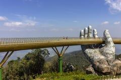 Da Nang, Vietname - 31 de outubro de 2018: Os turistas na ponte dourada, um passeio pedestre levantado por duas m?os gigantes, ab imagens de stock royalty free