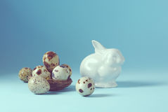 Da Páscoa do feriado fundo da vida ainda com os ovos brancos do coelho e de codorniz da porcelana no vintage decorativo do ninho  fotografia de stock royalty free