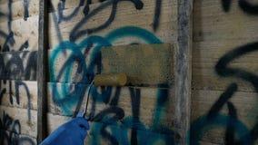 Da pessoa das pinturas da coberta grafittis acima na cerca video estoque