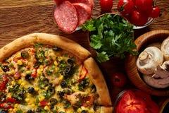 Da pizza vida ainda A peça da pizza recentemente cozida e dos seus componentes arranjou no fundo de madeira fotos de stock royalty free